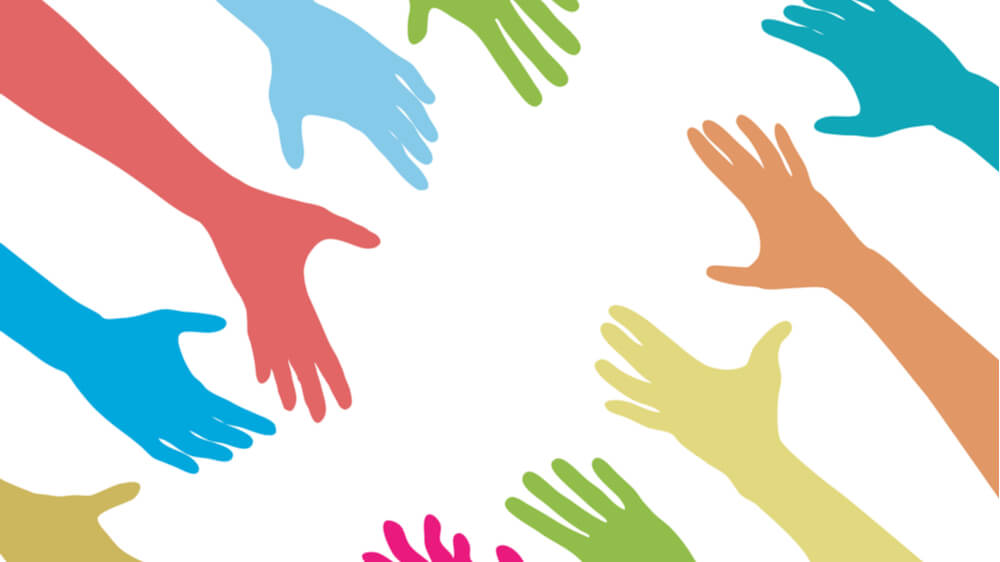 A range of multicolored hands (blue, green, orange, yellow, red) reaching out toward each other.
