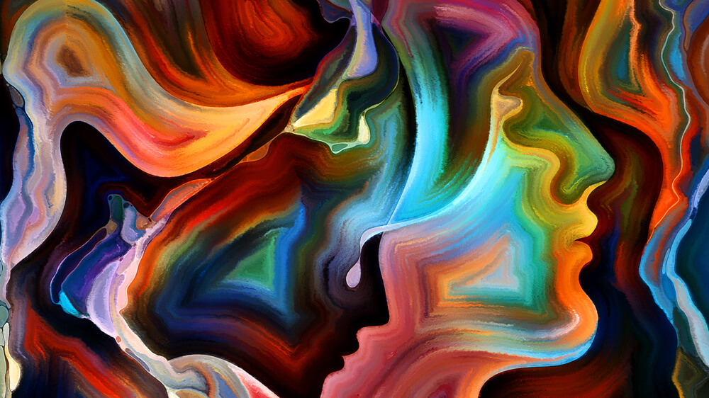 Arrangement of colorful paint and abstract shapes that look like human faces