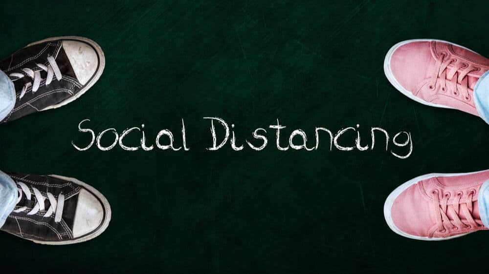 Two people standing on chalkboard with the word social distancing in between.