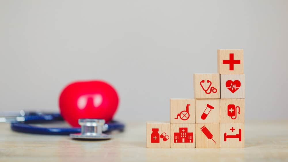 A photo of a stethoscope on a table next to building blocks with medical icons like a stethoscope and hospital bed to indicate building blocks of healthcare.