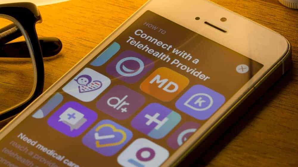 Mobile app icons of assorted telehealth providers from the App Store are seen on a smartphone.