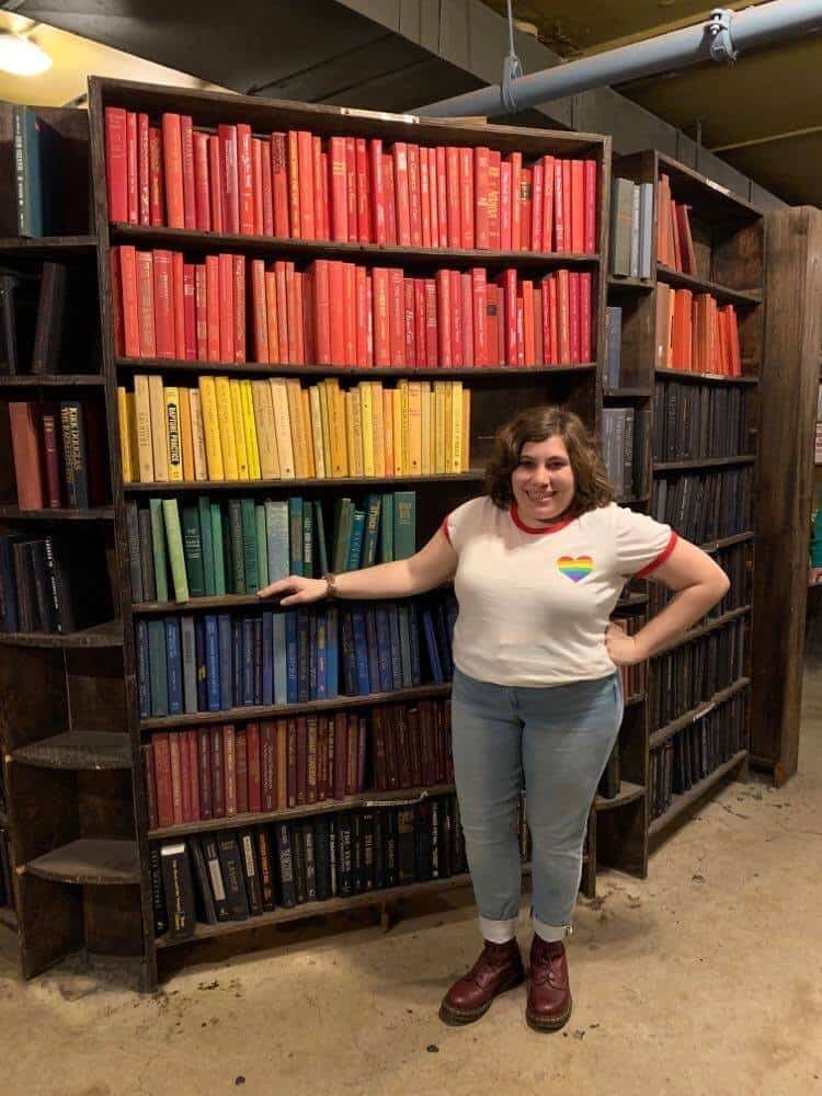 A young woman with short brown hair is standing in front of a tall bookshelf. The books are arranged in rainbow order. She is wearing a white T-shirt with a rainbow heart on the front, jeans, and red boots.
