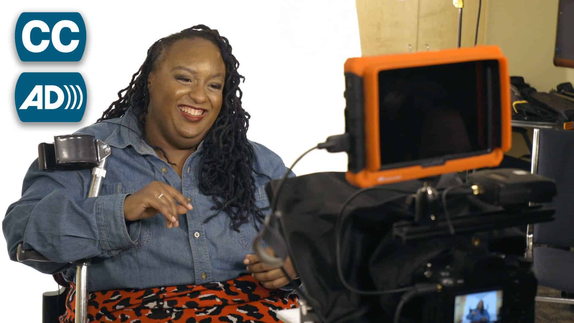 A Black woman with forearm crutches smiles widely on a film set.