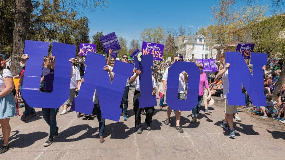 """A group of people marching down a street, holding big purple letters that spell """"union."""""""