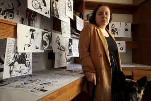 """A white female with short brown hair wears an oversized blazer as she leans on her black cane. Beside her is a long wooden desk that is consumed by 8"""" x 10"""" charcoal drawings of Disabled individuals. The head of her German Shepherd service dog can be seen tucked away in the lower right corner."""