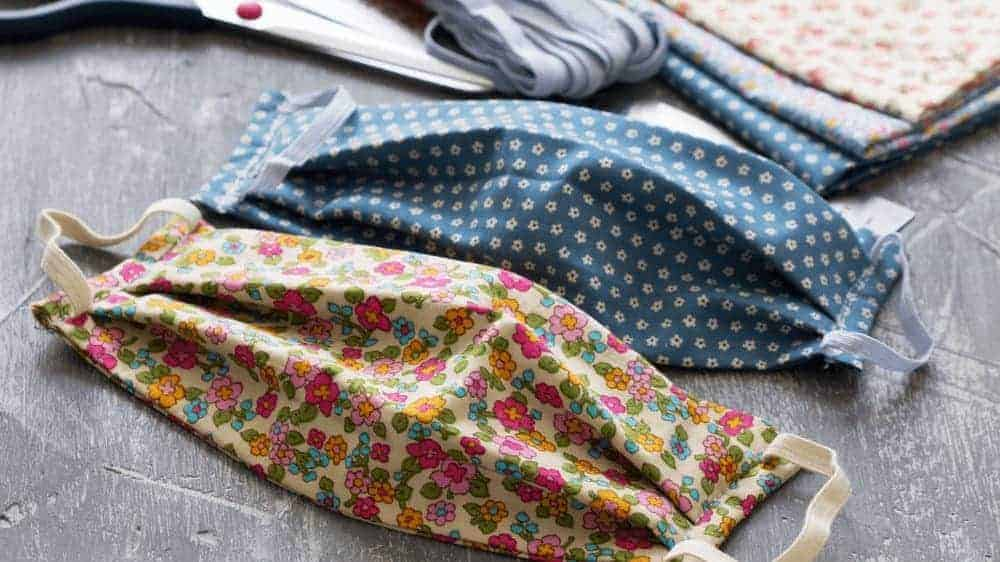 Homemade protective masks in floral patterns and pieces of cloth on a gray background.