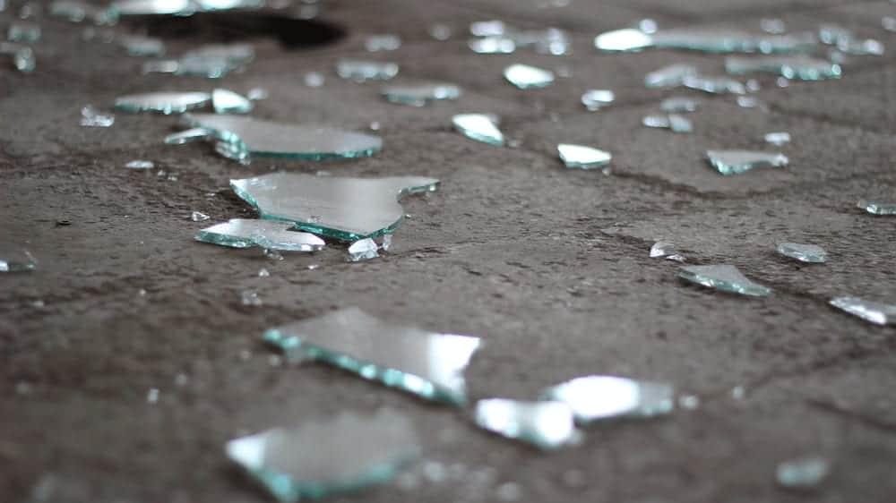 Shards of broken glass scattered on a gray floor.