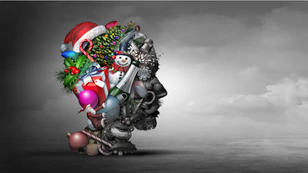 A shape of a person's head filled halfway with bright, colorful holiday items including a snowman, christmas tree, ornaments, and a santa hat, juxtaposed with greyed out items on the rest of the face. The background is a gray cloudy sky.