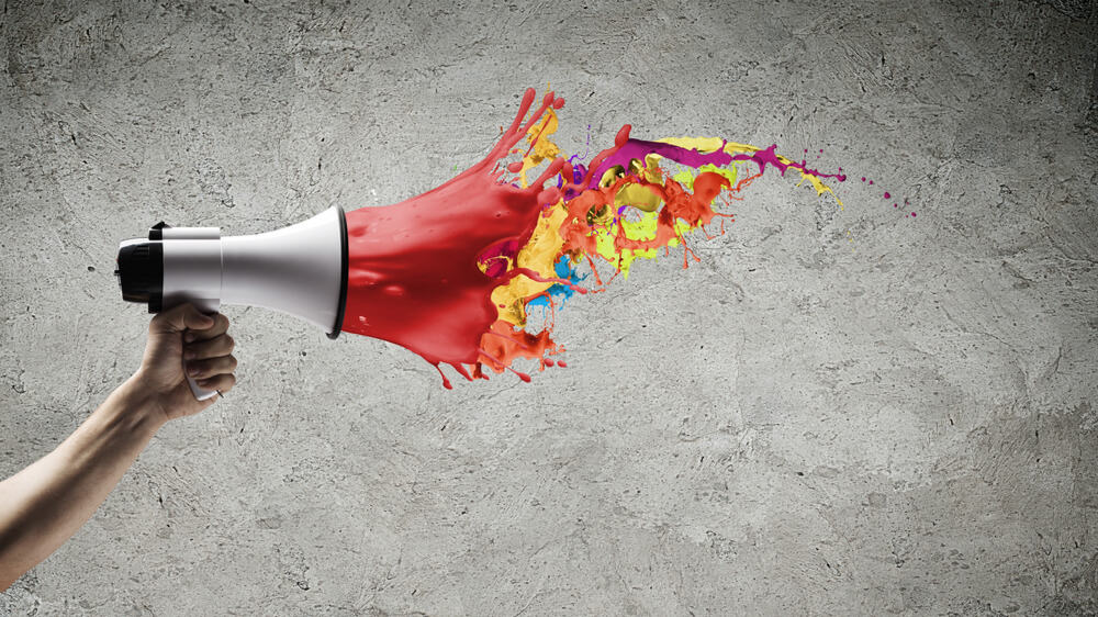 Hand holding a megaphone. The megaphone is white and red, and the red part fades off into multicolored paint splatters