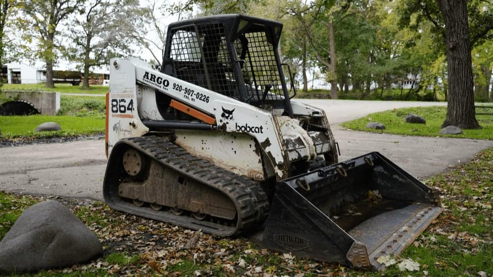 Bobcat Front track Skid loader surrounded by grass and fallen leaves.