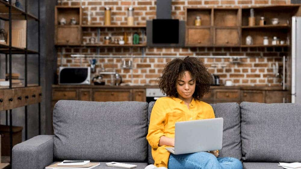 Young female-presenting person of color sitting on their couch with a laptop on their lap, working.