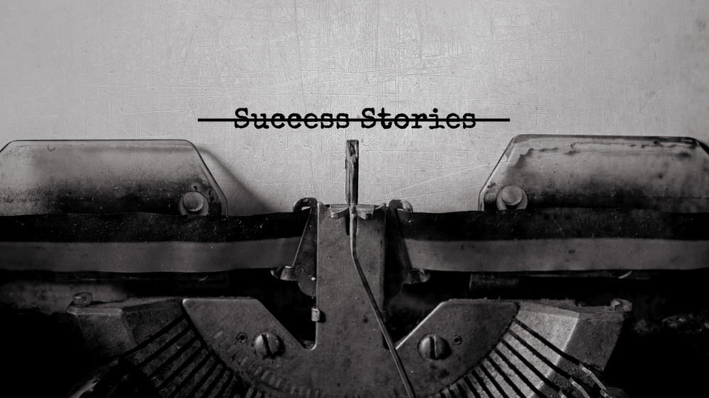 """A close-up of a typewriter with a piece of paper in it that says """"success stories."""" The words are crossed out with a black line."""