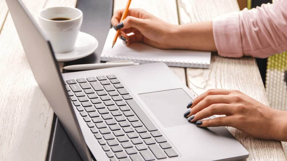 Closeup hands of white person in pastel pink shirt with painted nails working on laptop and making notes in their notebook, which is on wooden table with a laptop and a cup of coffee.