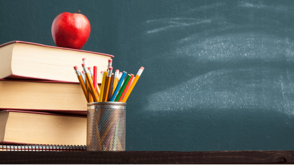 A pile of books with an apple on top and a cup with multi-colored pencils in it, in front of a chalkboard.