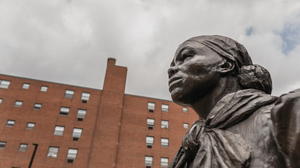 Against a background of a cloudy sky and brick building is the head of a statue of Harriet Tubman, taken from a lower angle so that the statue exudes strength and power.