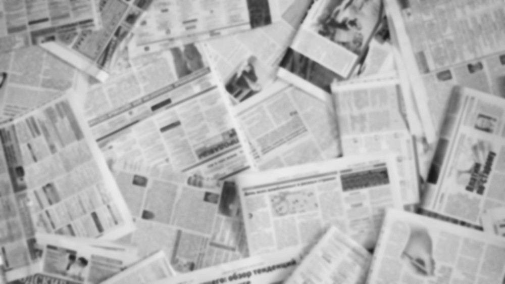 A blurred photo of a scattered pile of newspapers, printed all in black and white.