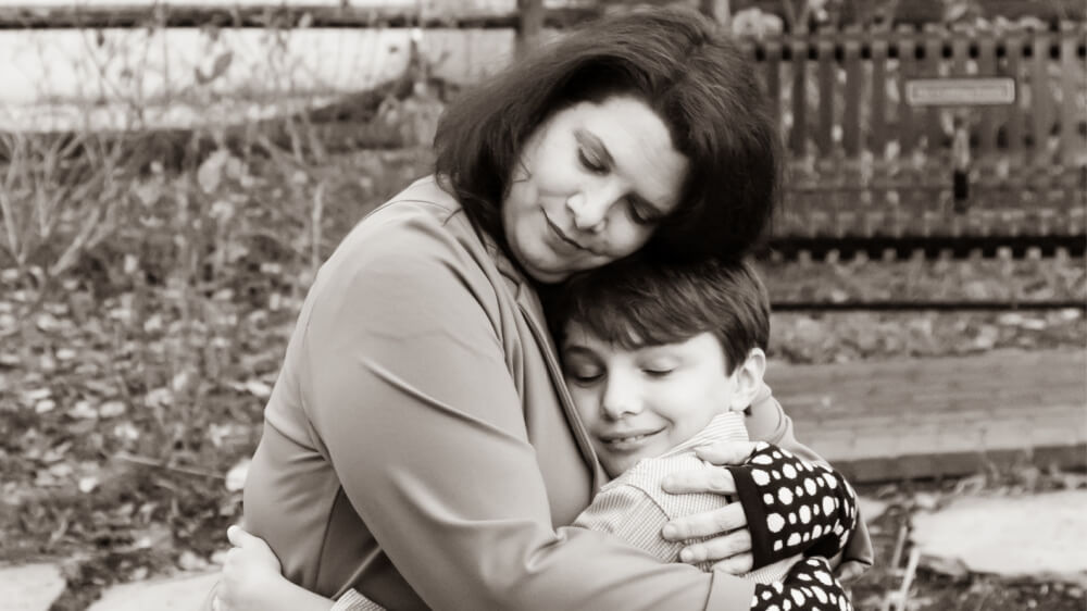 A grayscale photo of the author, a white woman with brown hair just above her shoulder, warmly hugging her son, a young white boy with close cropped brown hair.