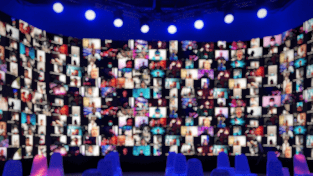 A wide rounded screen of blurred faces, all on webcam, under a row of spotlights.