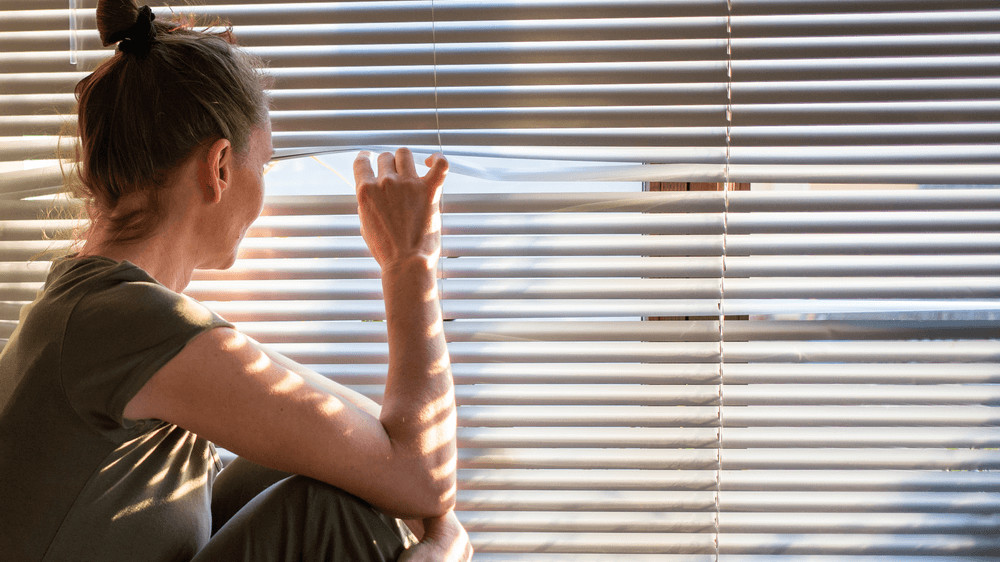 A white woman sitting next to closed blinds, using her fingers to open them and peek through the window to outside.