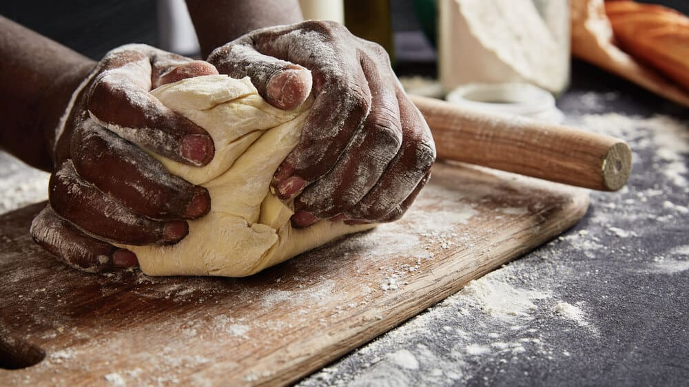 A Black person's hands kneading dough on a floured surface.