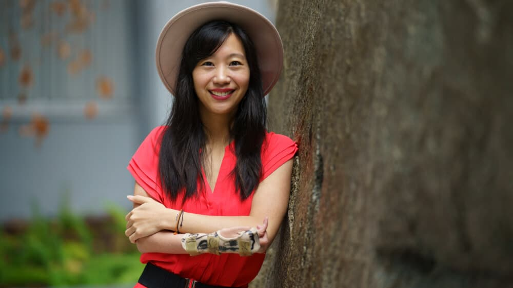 Photo of Tiffany, an Asian woman with dark hair below her shoulders, leaning against a tree. She is wearing a hat and a red top. Her arms are crossed, and she is wearing a splint.