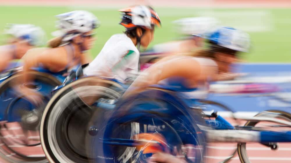A blurred photo of wheelchair racers in motion.